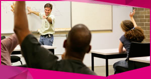 A teacher at a whiteboard taking questions from his students during his course