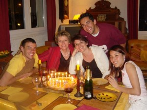 People sitting at a dining table around a candle lit cake